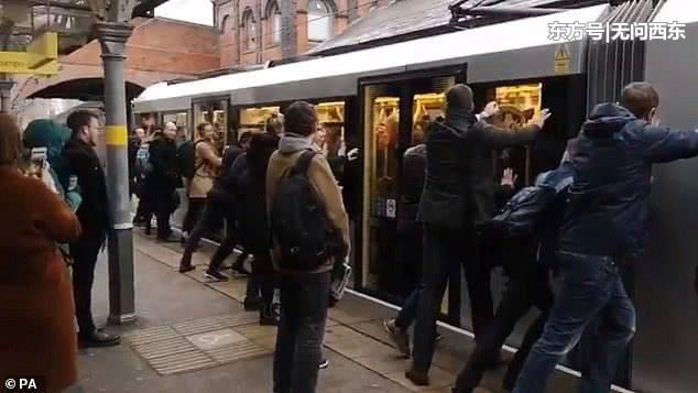 城铁挤到开不动 ,乘客动手推列车
