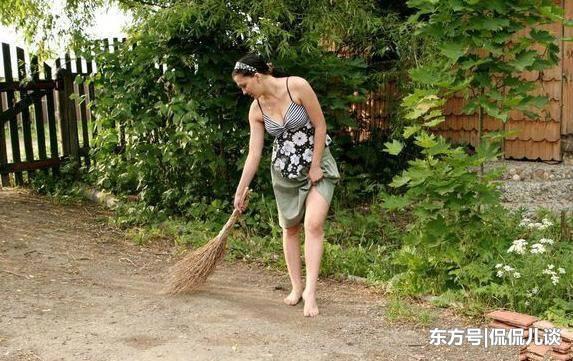俄罗斯的乡下生活:妇女光着脚穿裙子打扫院子