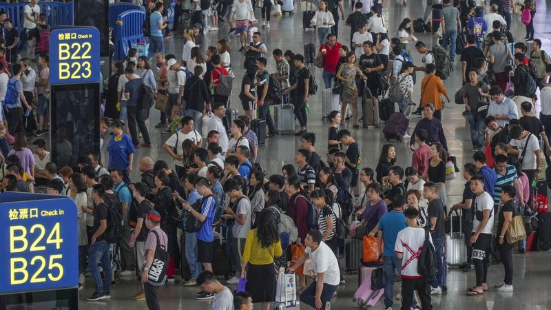 China's rail operator apologises for holiday travel chaos but says it will seek to punish unruly passengers