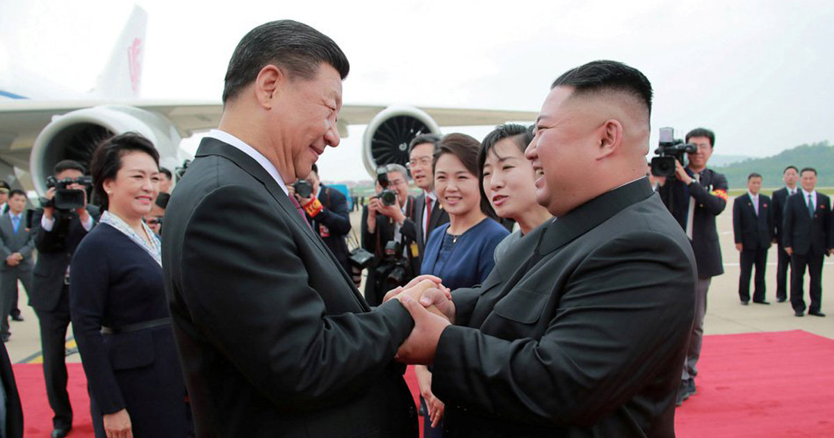 North Koreans sing 'I love you, China' & form Xi Jinping's face in stadium to welcome him