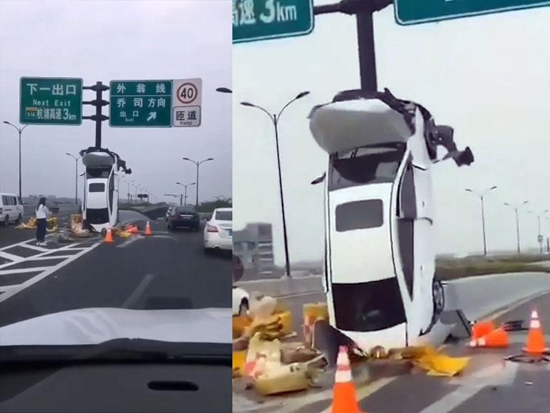 奇景!汽车出意外垂直靠在路牌杆 车上3人安全下车