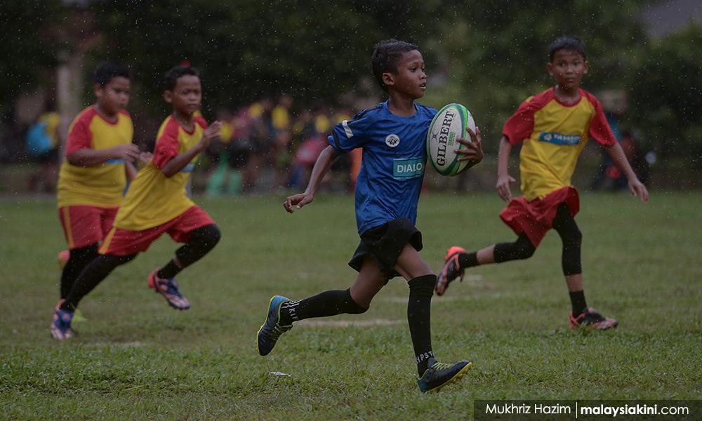 SK Bukit Lanjan rugby team carries the ball for Orang Asli
