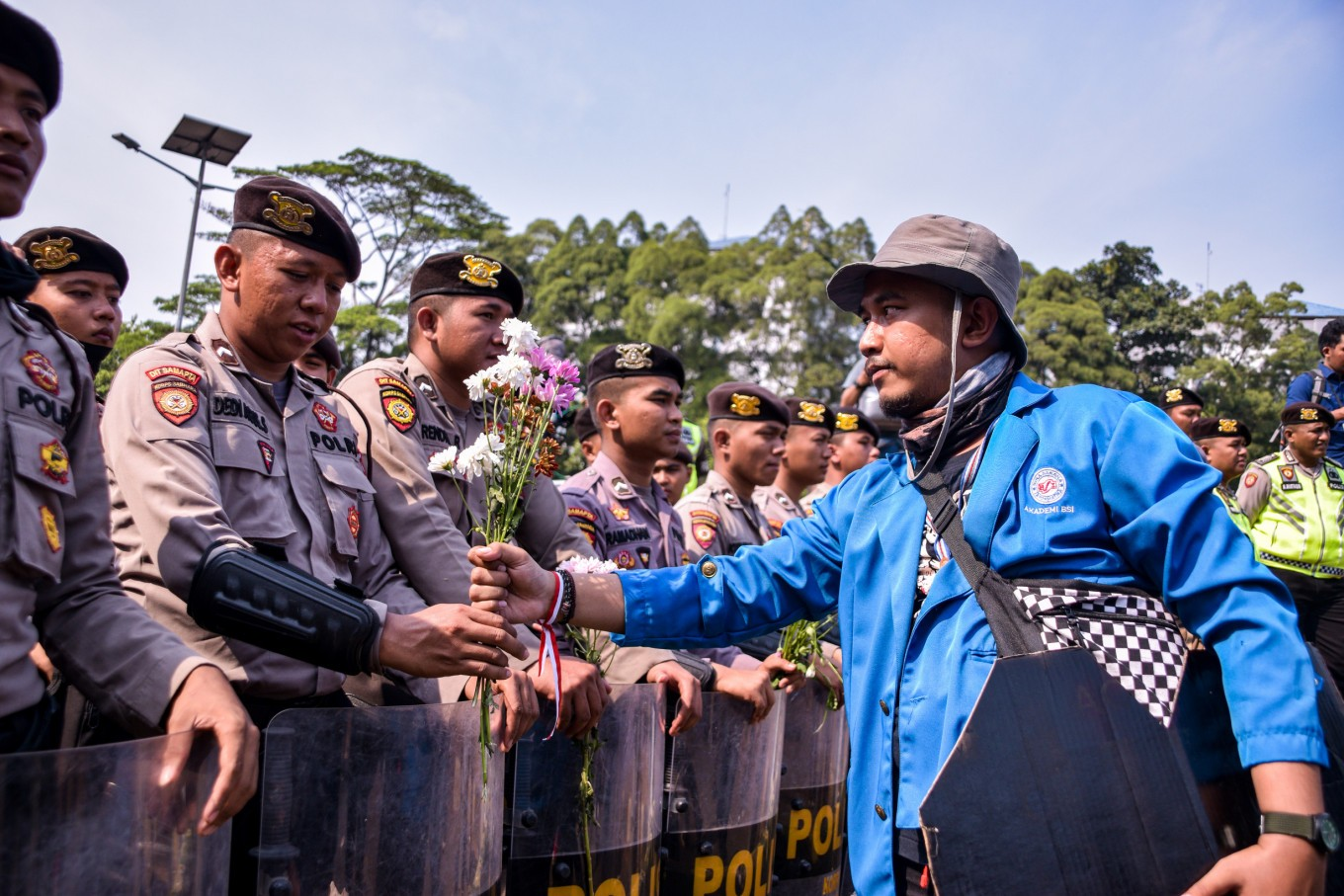 Flower power: Students in Jakarta hand out blossoms as sign of peaceful protests