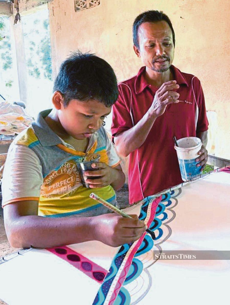 Boy helps dad in home-based batik printing biz