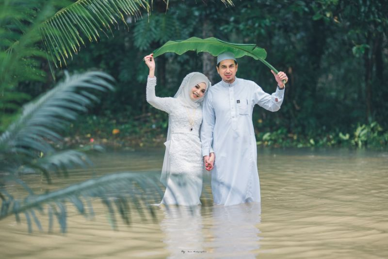 Couple in southern Thailand pose in knee-deep floodwater for wedding photoshoot during monsoon season