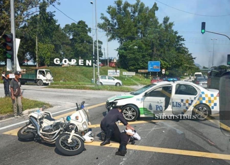 Traffic police officer injured after police escort car hit him in Kampar