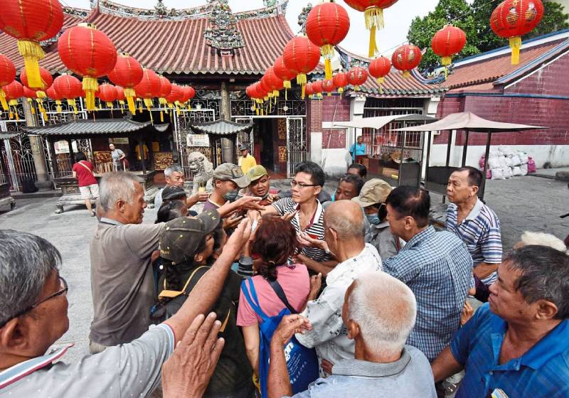 Malaysian man handing out donation at temple is mobbed by 'habitual beggars'
