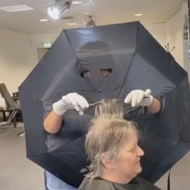 Hairdresser cuts holes in umbrella for arms and eyes as barrier between clients