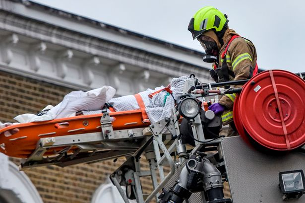 Coronavirus patient air-lifted out of flat window by firefighters in masks