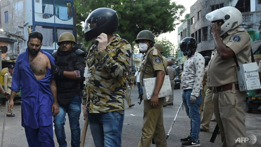 Migrant workers throw stones at police in India in protest against lockdown