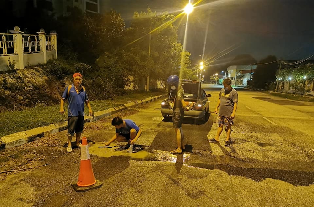 Fed up with potholes, Bercham residents in Ipoh patch road up themselves