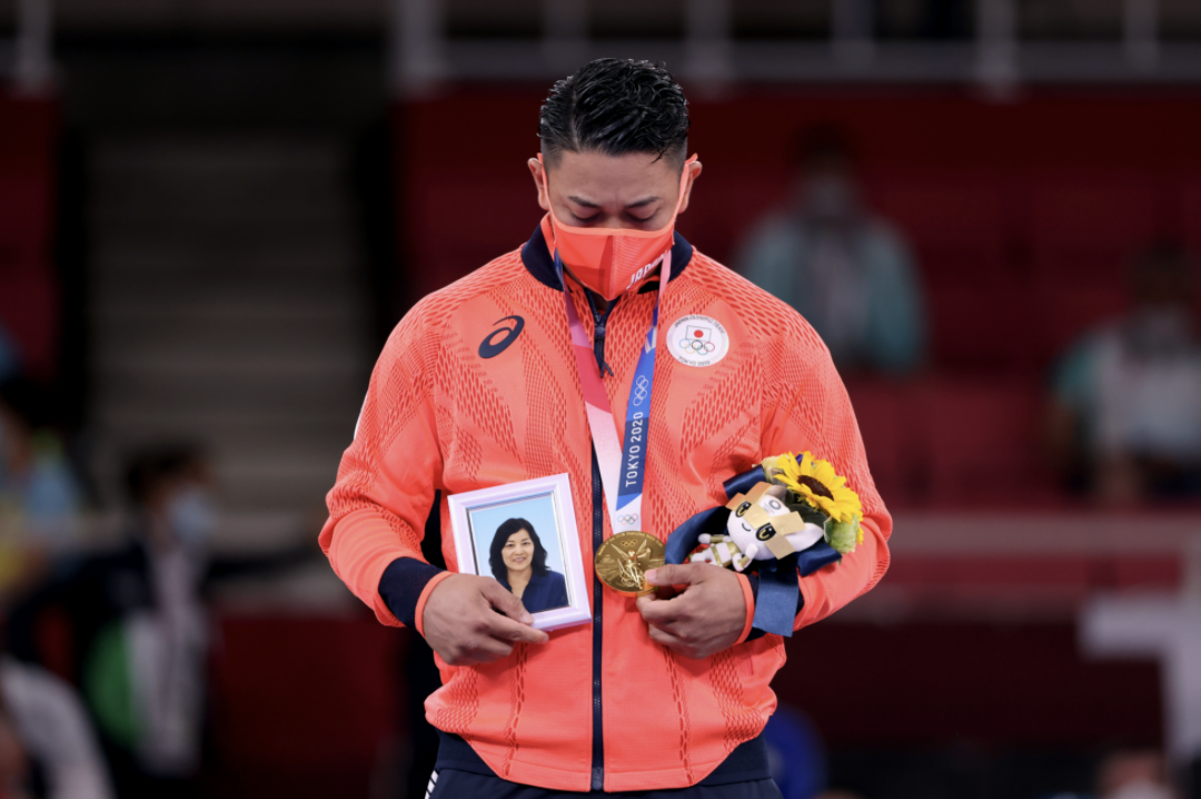 Olympic gold medallist takes photo of dead mother to podium in touching tribute - 'Crying in heaven'