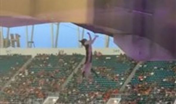 Dramatic moment football fans catch cat dangling from upper stadium stand